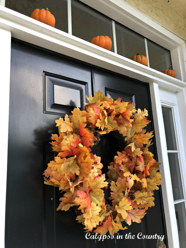 Black front door with orange fall wreath and mini pumpkins above