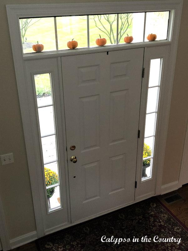 Mini Pumpkins above front door for fall