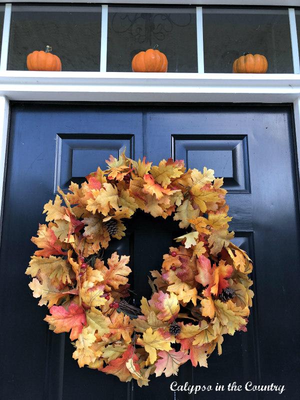 Mini Pumpkins over black door with fall wreath - Autumn Porch Decor