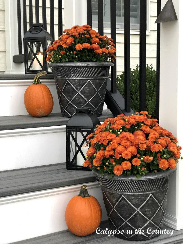 Orange mums and lanterns on back porch steps