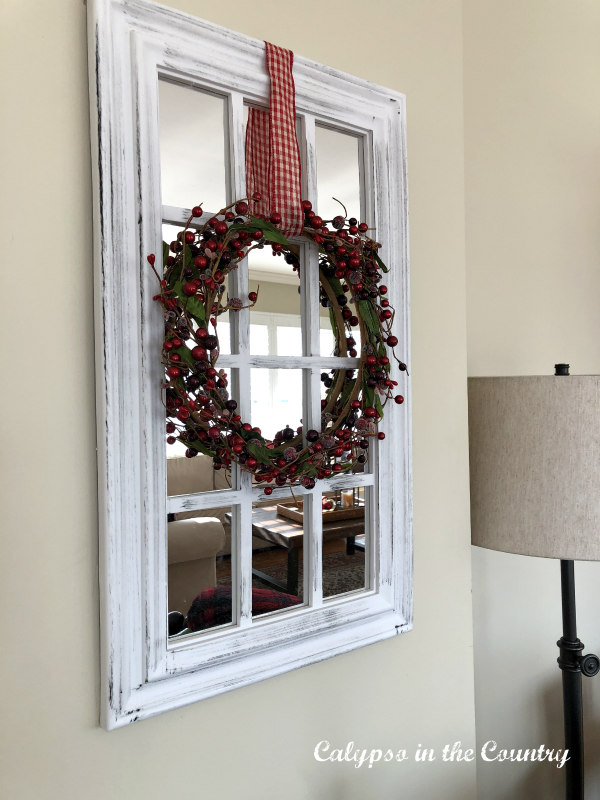 Red berry wreath on window pane mirror