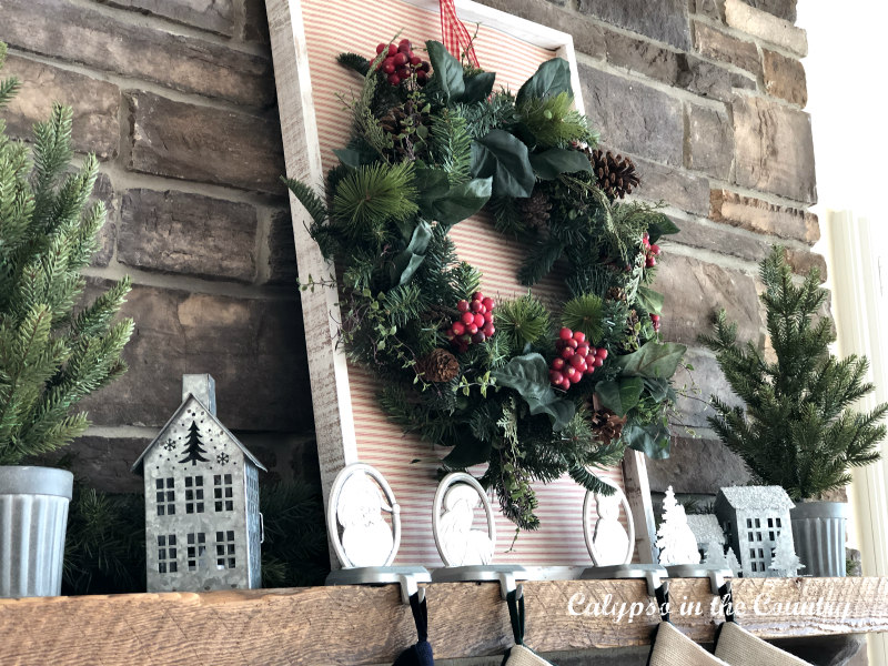 Christmas wreath with red berries and galvanized houses on mantel