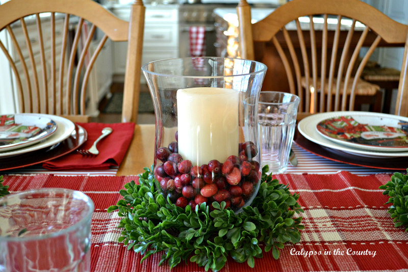 Glass hurricane with cranberries on Christmas table