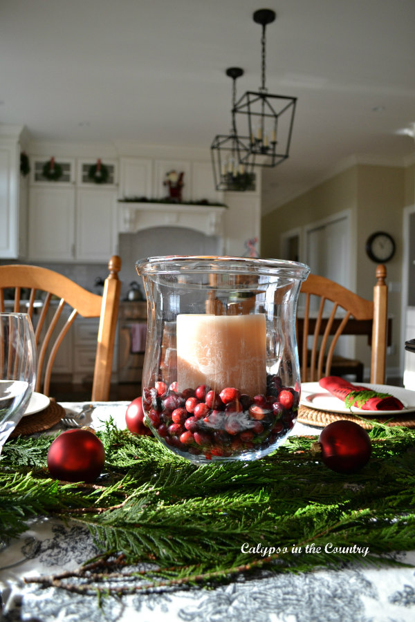 Glass hurricane with candle and cranberries on Christmas table