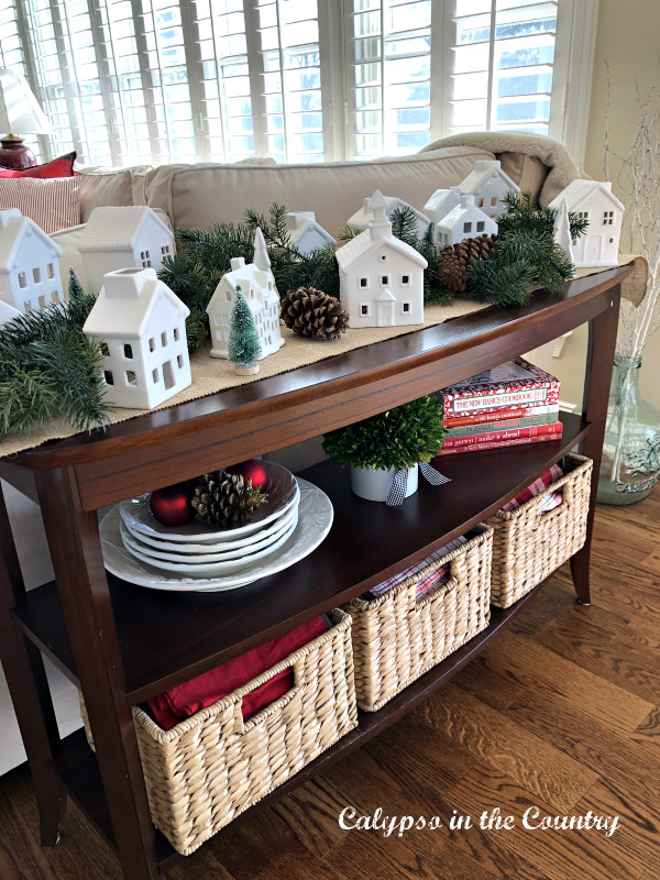 White ceramic Christmas village on sofa table