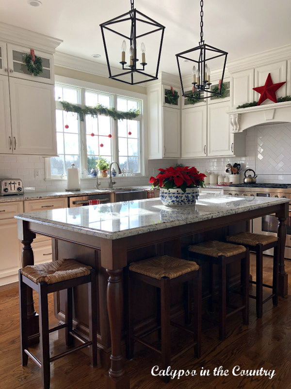 Kitchen island in white kitchen decorated for Christmas