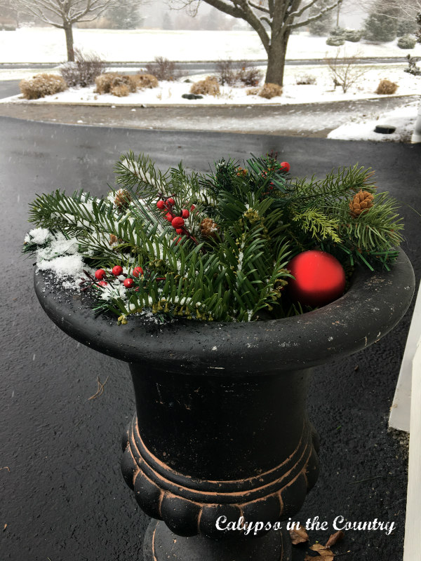 Red Christmas ornaments and greenery in black urn