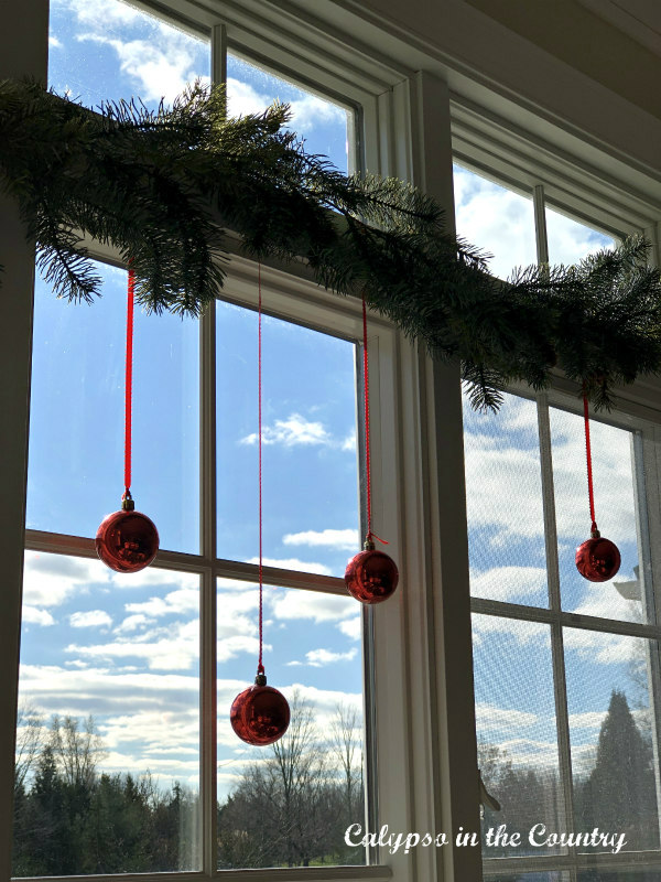 Red Christmas ornaments hanging in window