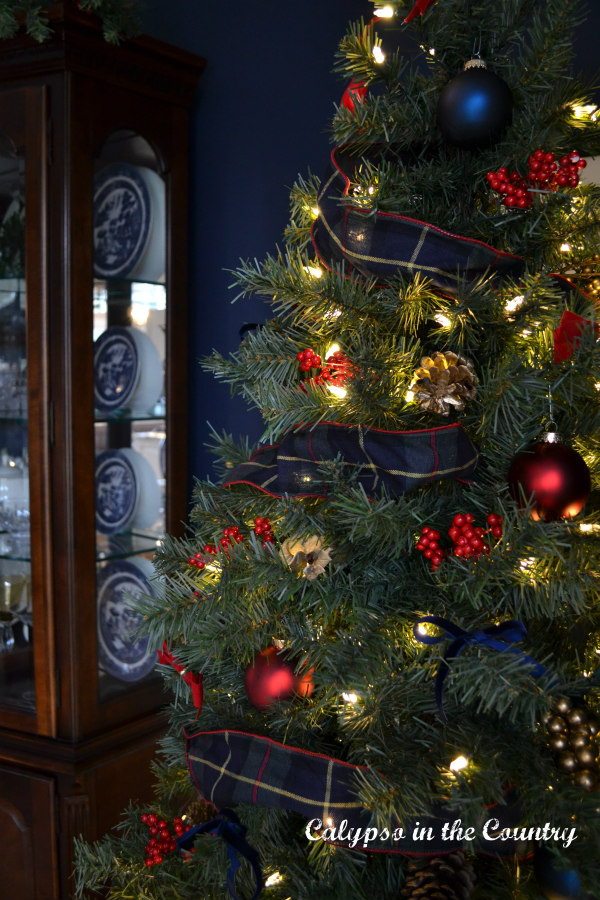 Red and Blue Christmas tree next to china cabinet