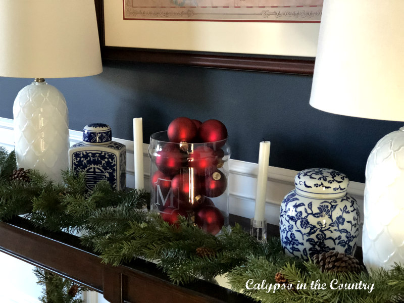 Red Christmas ornaments in glass container on table with blue and white porcelain