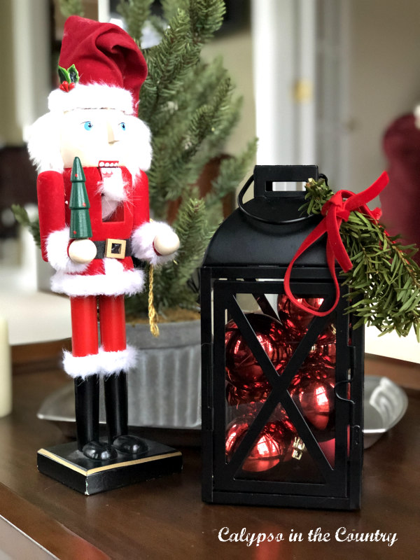Santa nutcracker and black lantern filled with red ornaments