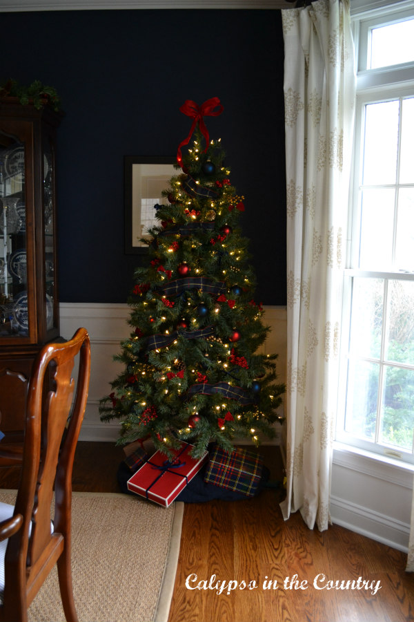Red and Blue Christmas tree in corner of navy dining room