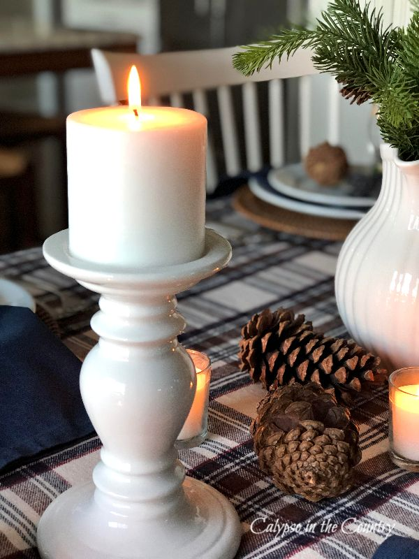 White burning candle on plaid tablecloth
