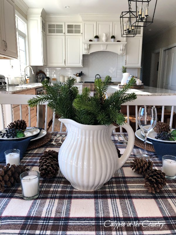 White pitcher centerpiece filled with winter greenery - simple and cozy winter tablescape