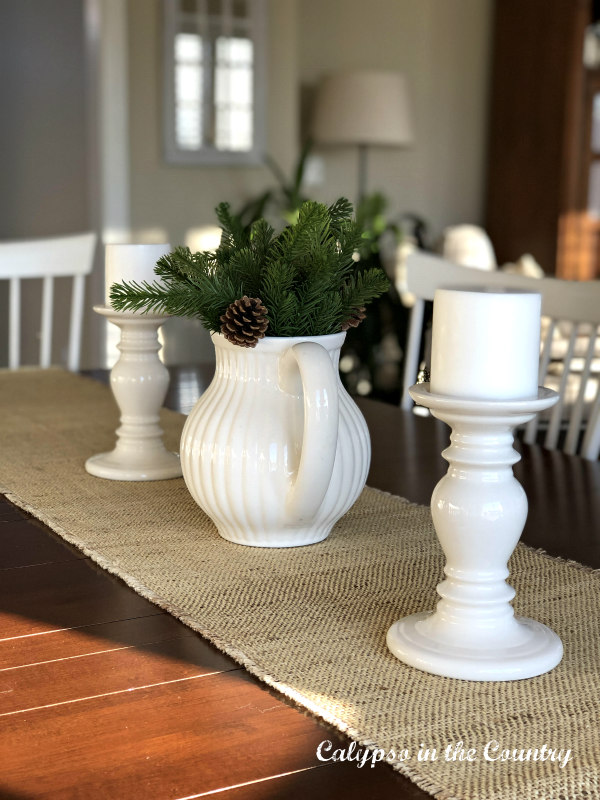 White candles and white pitcher with greenery