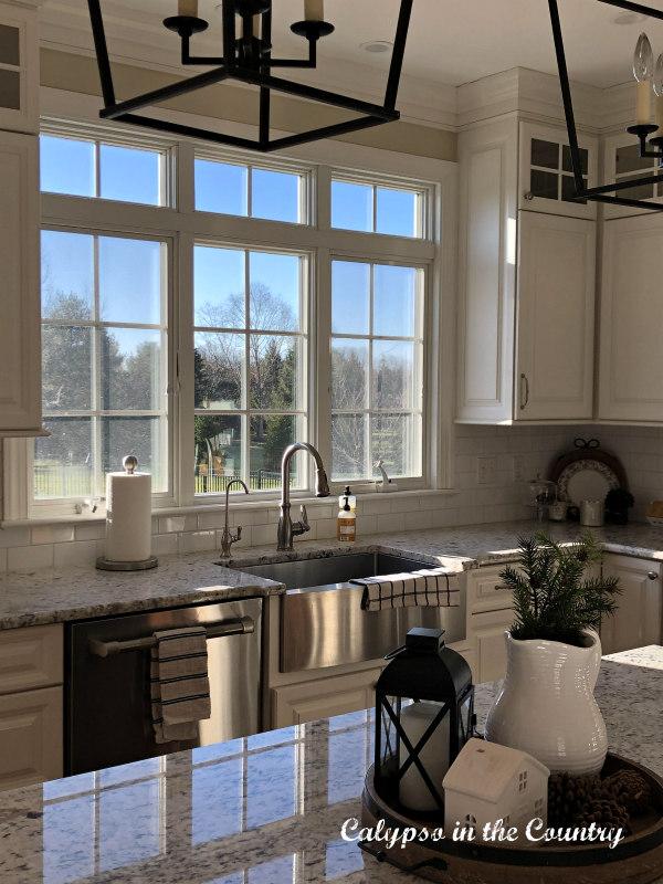Kitchen window in white kitchen decorated for winter