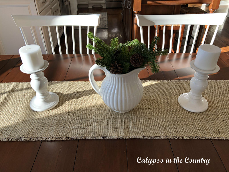 White pitcher and candles on burlap table runner
