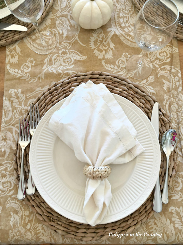 White napkin on white plate and round woven placemats