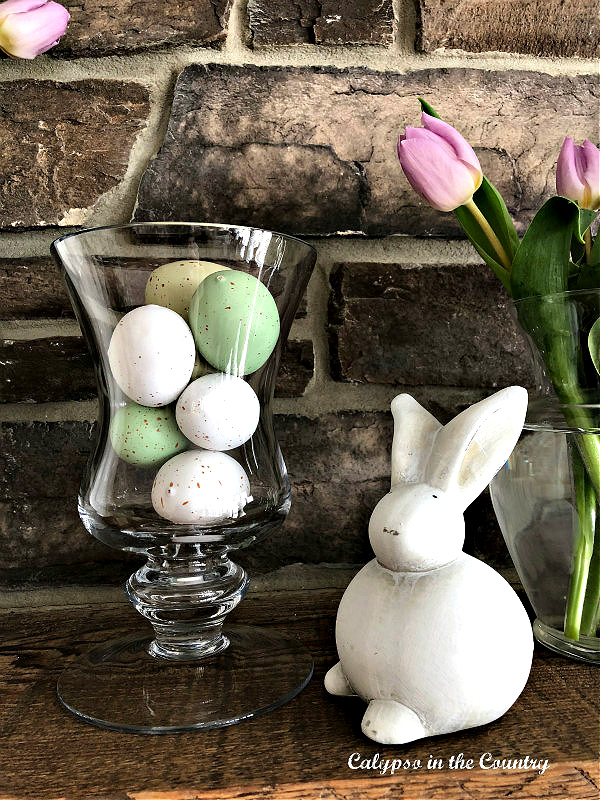 vase with Easter eggs next to ceramic bunny on mantel