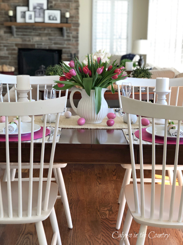 Wood dining table with white chairs and pink tulips