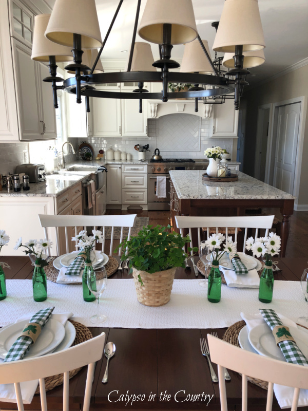 St. Patrick's Day table setting with shamrocks and green bottles