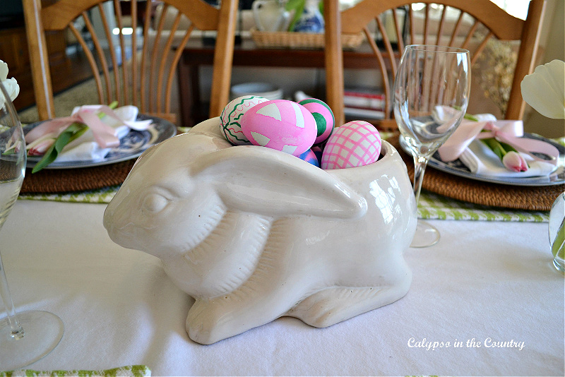 White ceramic bunny planter filled with colorful Easter eggs