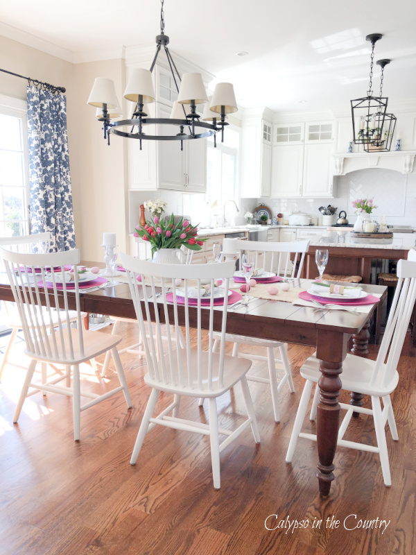 White kitchen with table set with pink for Easter