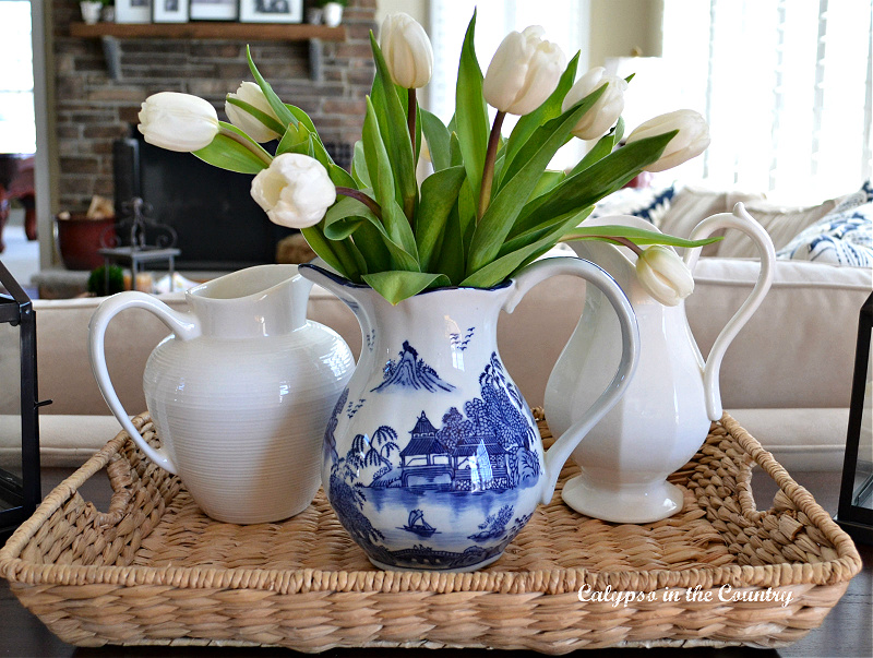 White tulips in blue and white pitcher on seagrass tray