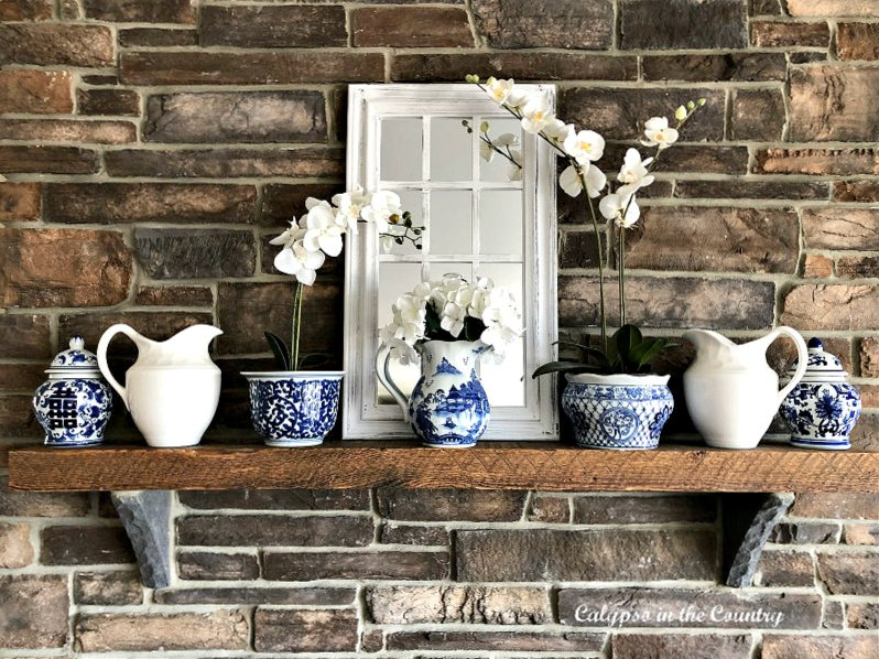 Blue and white porcelain and white orchids on fireplace mantel