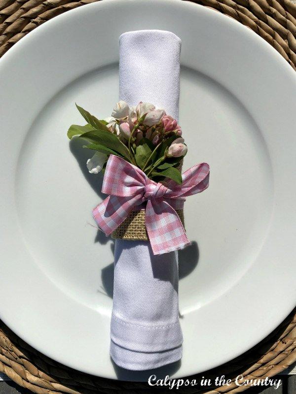 Pink gingham ribbon tied around a DIY napkin ring