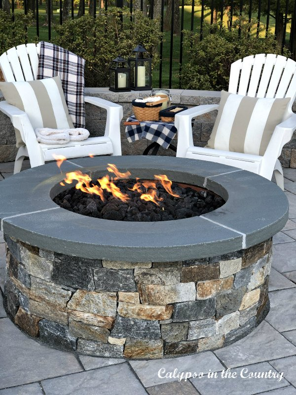 stone firepit and white adirondack chairs - ideas for outdoor entertaining areas
