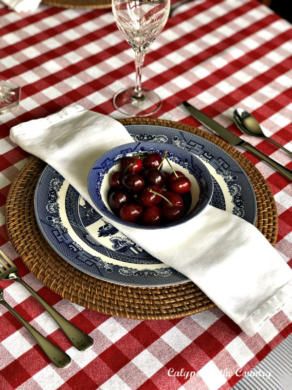 Red and White buffalo checked tablecloth with blue plates and a bowl of red cherries