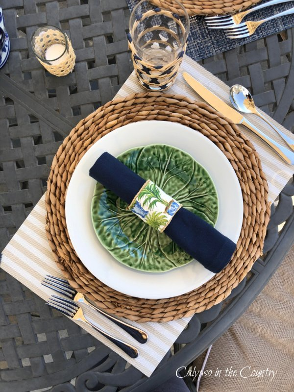 Place setting with green and white plates and navy rolled napkin