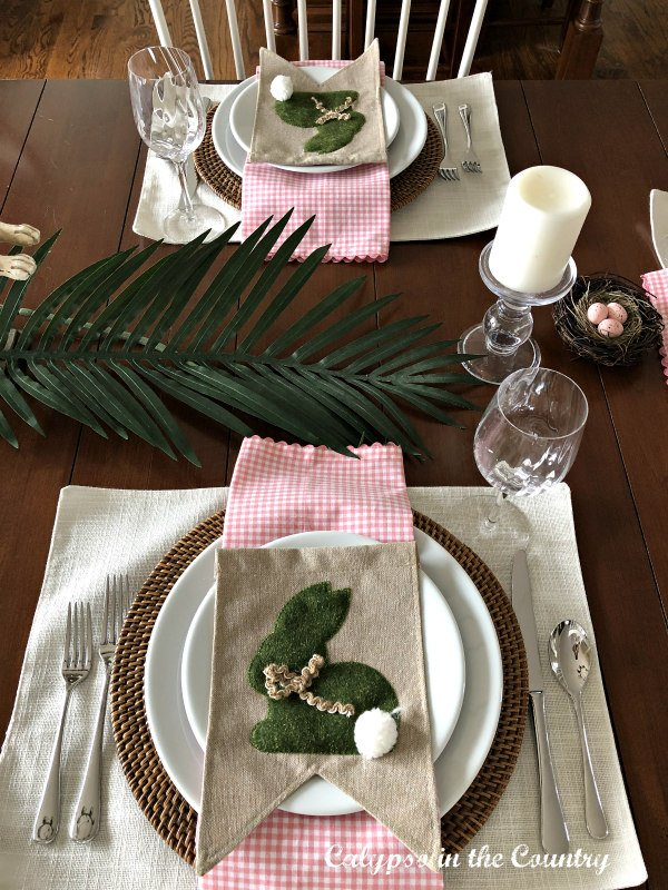 Pink gingham napkins and burlap bunnies on white plates