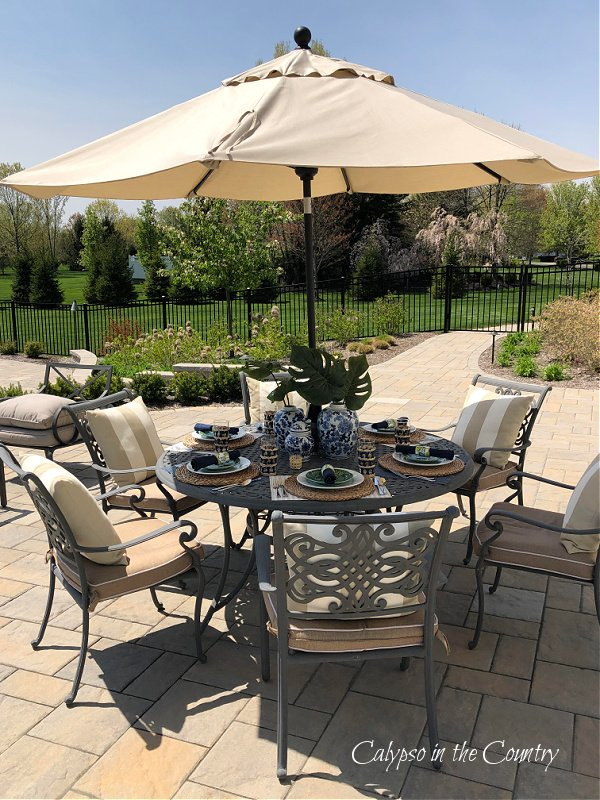outdoor table with umbrella on stone patio - Mother's Day Table Setting Decor