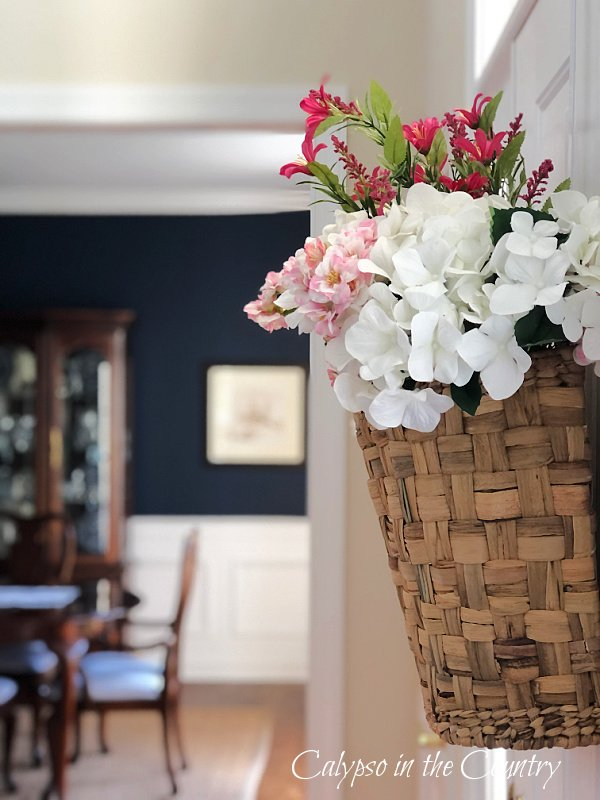 Basket of flowers hanging on inside of door - Spring entryway ideas