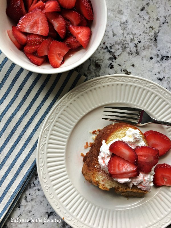 poundcake with strawberries and whipped cream on white plate