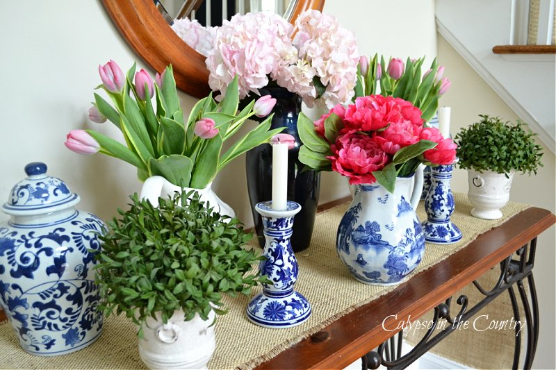 Pink flowers and blue and white porcelain on table - how to decorate an entry table for spring