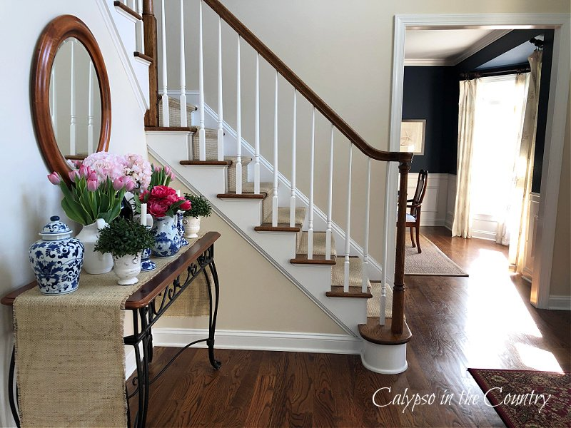 Staircase and foyer with entry table decorated for spring