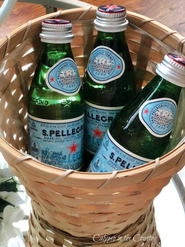 basket of pelligrino water bottles - bar cart styling tips
