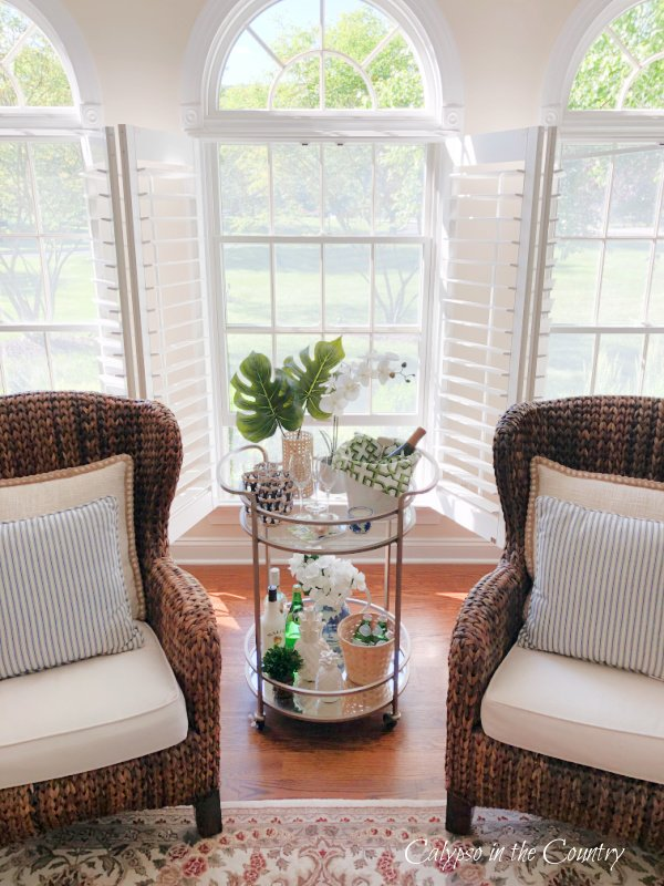 open plantation shutters seagrass chairs and tropical bar cart styling tips