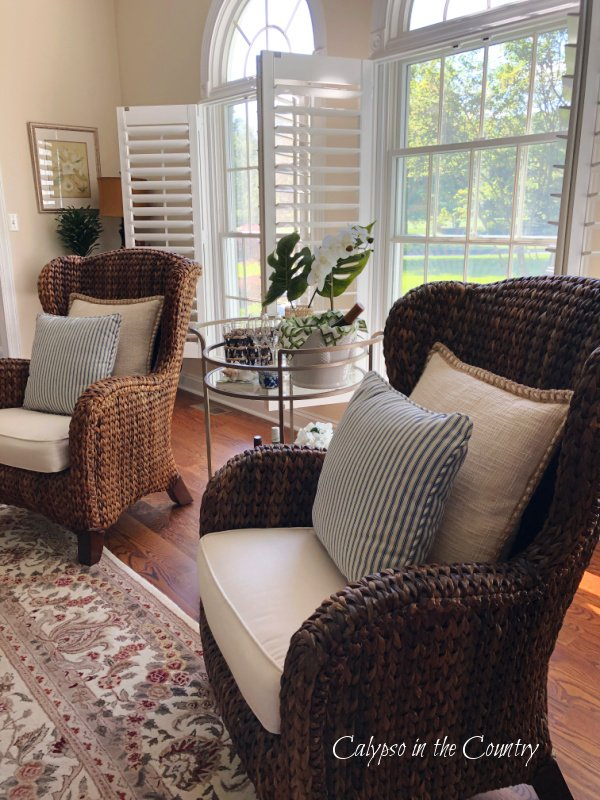 seagrass chairs and plantation shutters with tropical bar cart tips