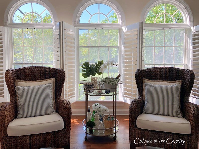 seagrass chairs and tropical bar cart in front of three open windows with plantation shutters