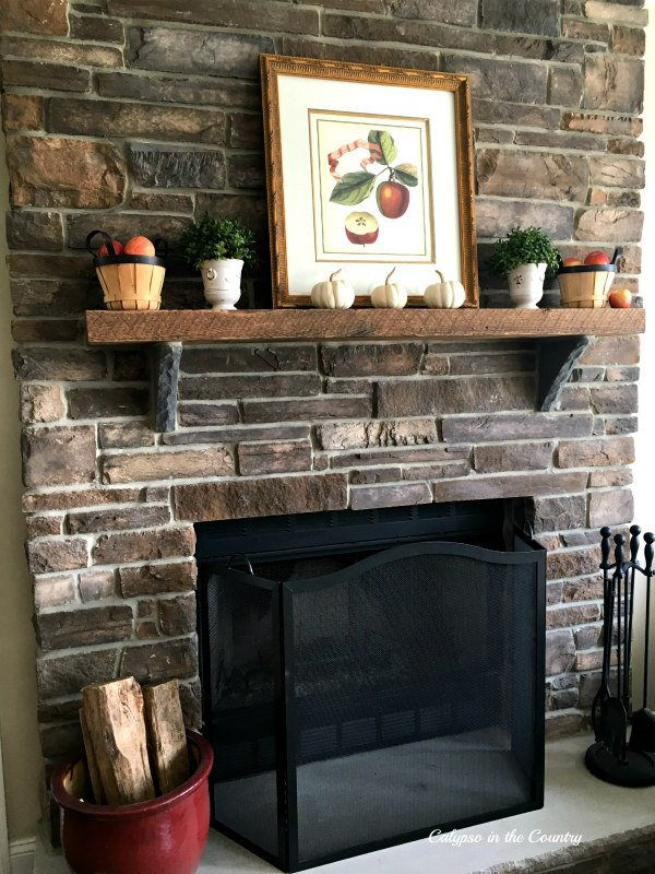 stone fireplace with mantel decorated for fall