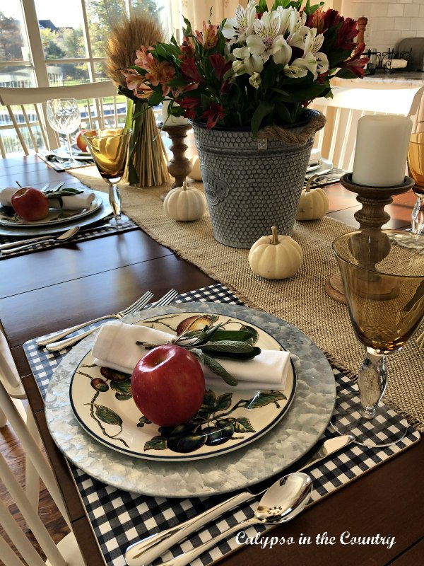 White pumpkins and apples on table setting for fall